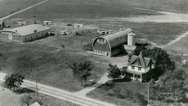 This photograph shows an aerial view of the Whiting airport. It was located at what is now Appleton Road and Airport Road in Menasha. The hanger is on the left and is part of the Kitz & Pfeil Hardware Store.