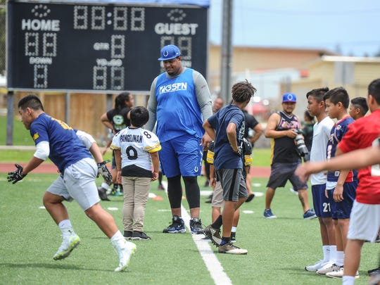 Chamorro NFL draft pick Zach Banner towers in height in comparsion to aspiring football athletes during the Zach Banner Football Festival held at Guam High School in Agana Heights on Thursday, July 6, 2017.