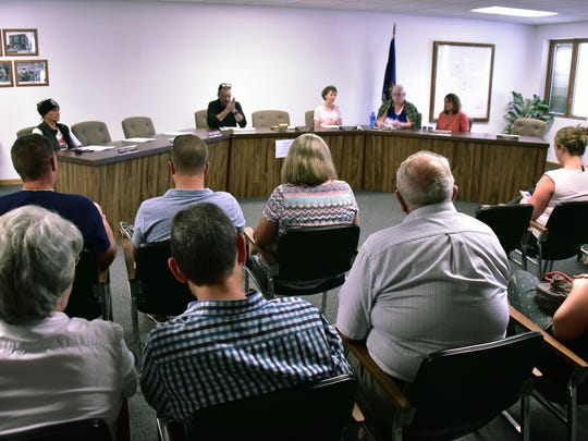 Above, left: Village officials and trustees wait for other members of the council to arrive for a meeting, but three members did not show, forcing the meeting to be canceled.Right: Rallies and protests over the remarks have been staged at the fountain.