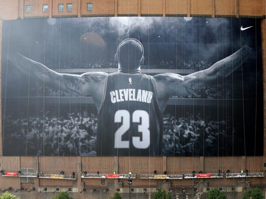 FILE - In this Oct. 30, 2014, file photo, workers finish hanging a mural of Cleveland Cavaliers' LeBron James on a building in Cleveland. The colossal LeBron James banner is getting a small _ but significant _ upgrade. The iconic, 10-stories-tall mural is being removed this week and replaced with a new one that includes a gold patch of the Larry O'Brien Trophy on the back of James' uniform to represent the Cavaliers winning the NBA title last season to end the city's 52-year championship drought. The new banner is expected to be installed by Friday, Oct. 21, 2016. (AP Photo/Mark Duncan, File)