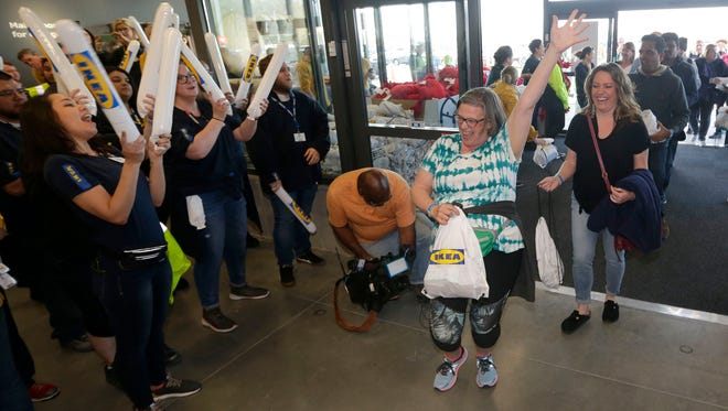 Patricia Gieringer of Menomonee Falls celebrates and employees cheer as she enters IKEA on Wednesday morning with her friend, Shanna Bremer (right), also of Menomonee Falls.