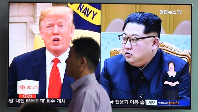 A man at a train station in Seoul, South Korea, walks past a television news screen showing President Trump and North Korean leader Kim Jong Un.