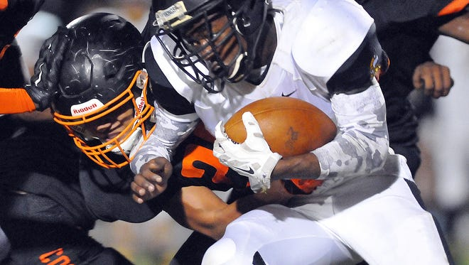 Cocoa High's #21 Zach Beagle takes down Bishop RB #1 William Scott III during Friday night playoff game against Bishop Verot held at Cocoa Tiger Stadium .