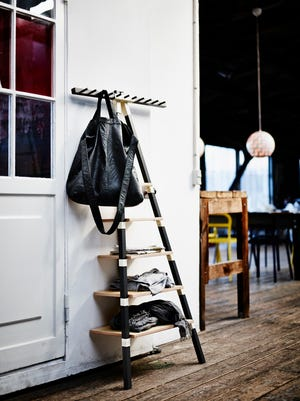 This photo provided by Ikea shows a wall shelf with lots of knobs from P.S. 2014's collection, designed for the mobile resident. Available in birch or anthracite/birch, the piece provides storage and hanging space in one unit.