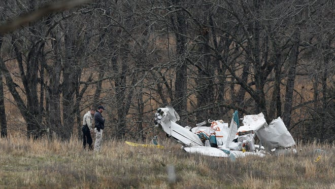Officials investigate the scene of a plane crash on Monday morning that occurred Sunday in a field off of Yocum Pond Road near Branson.