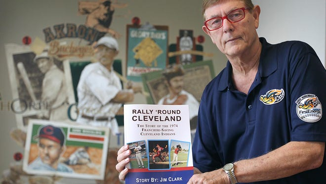 """Akron RubberDucks radio broadcaster Jim Clark holds a copy of his book """"Rally Round Cleveland."""""""