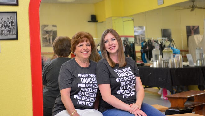"""Artistic Director Stephanie Medenwaldt (right) became the new """"Keeper of the Mirror"""" today at Dance, Etc., as studio founder and owner Reggie Milam announced her retirement, and that Medenwaldt is the studio's new owner. The mirror dates back to a ballet studio in Russia from the 1870s."""