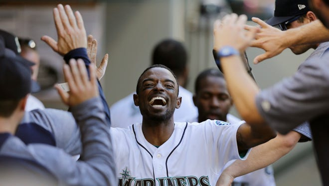 Dee Gordon celebrates after scoring against the Boston Red Sox during the third inning of Saturday's game in Seattle.