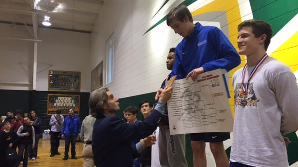 Asheville School wrestling coach Lecky Haller presents Conor Fenn with his state championship award at last weekend's NCISAA tournament in Arden.