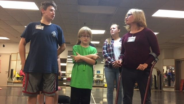 "Thomas Medvecz (left), Xavier Roberts (center), and Elizabeth Blenker (right) rehearse a scene from ""Seussical Jr."" with their mentors behind them."