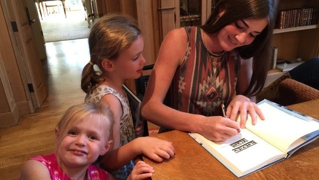 Jacqueline Frist signs a copy of her book for family friends Ella Grace Kidd, left, and Mary Katherine Kidd.
