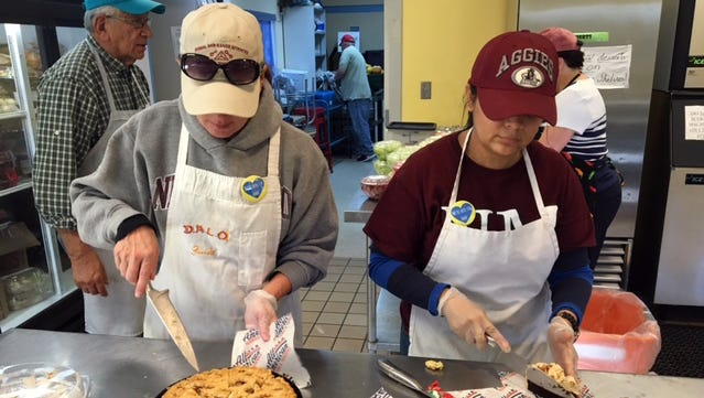 New Mexico State University staff members Kristie Garcia, left, and Desma Montellano prepare meals at El Caldito soup kitchen. A number of volunteers from NMSU recently volunteered at El Caldito in memory of staff member Ann Palormo, who died in in November.