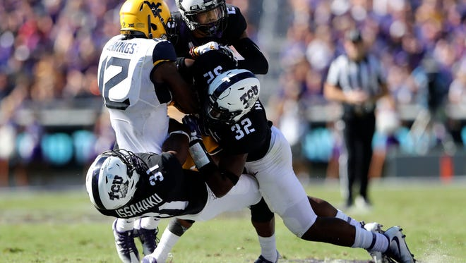 West Virginia Mountaineers wide receiver Gary Jennings (12) is tackled by TCU Horned Frogs safety Ridwan Issahaku (31) and linebacker Travin Howard (32) during the first half at Amon G. Carter Stadium.