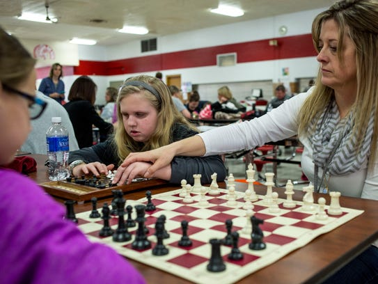 Avery Shutt, 9, uses a braille chess board as Nicole