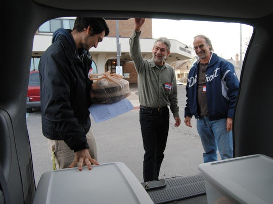 Port Huron son and father Tony, left, and Mike Mercatante, right, with friend Mark Smith ready Christmas meals to deliver from the back of their minivan on Friday, Dec. 25.