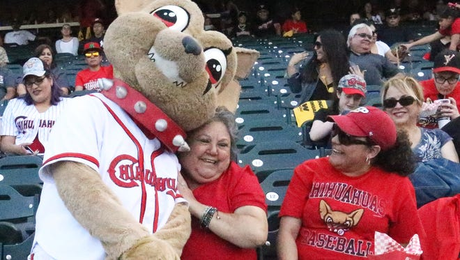 Chico the El Paso Chihuahuas mascot snuggles up to Elvia Maisonet, center, before the start of the team's home opener against the Reno Aces on Friday night at Southwest University Park. Maisonet and her daughter, Kimberly Maisonet, right, are season ticket holders.