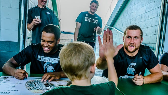 MSU tight end Matt Sokol, right, high-fives a young fan Tuesday in East Lansing.