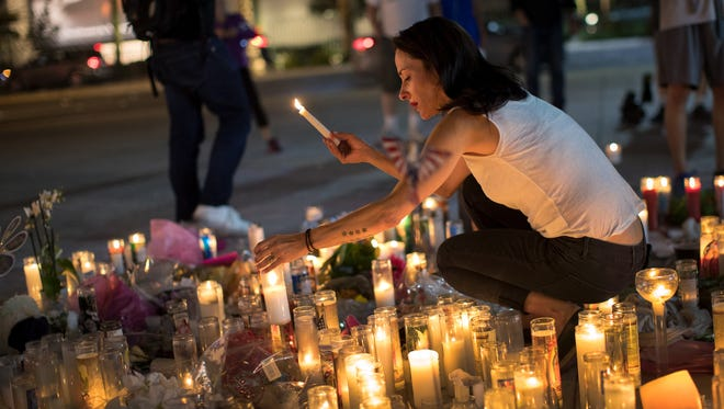 Las Vegas resident Elisabeth Apcar lights candles at a makeshift memorial at the northern end of the Last Vegas Strip, Oct. 4, 2017 in Las Vegas, Nev. for victim of mass shooting.