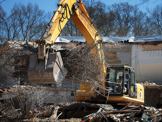 A demolition specialist clears away debris from the north side of the old Collierville High School building where workers are currently demolishing an old, unused portion of the building. The main part of the building will remain intact.