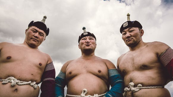 Three Kazakh wrestlers photographed at a wedding in