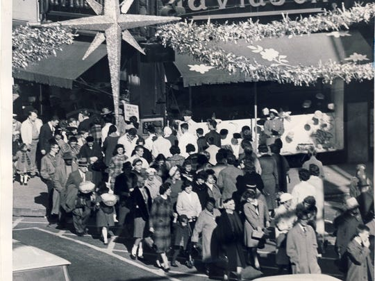 """A glittering """"Star of Hope for merchants"""" hangs over Christmas shoppers crossing Guthrie Street at Fourth Street on Nov. 24, 1961, after Thanksgiving."""
