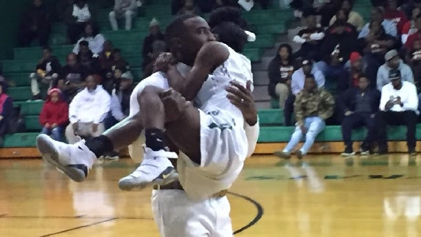 Bossier coach DeShawn Williams totes injured player Chloe Walker to the bench during Tuesday's game with Minden. Walker later returned to the contest.