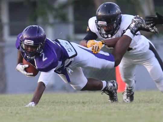 Cypress Lake's Isaiah Thomas is tackled by Bishop Verot's Anthony Moore during a spring football game at Cypress Lake High School on Wednesday.
