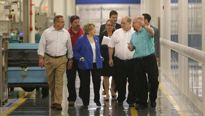Congresswoman Louise Slaughter  listens as Rocco D'Angelo, manager for the injector area, explains  parts of the injector manufacturing including the clean room during a tour at the GM plant in Rochester.