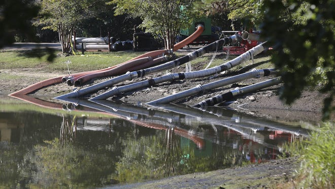 Work crews use an pumps to lower water levels and stabilize a dam at a lake, Wednesday, Oct. 7, 2015, in Columbia, S.C. Heavy rain has caused flooding in parts of the state. (AP Photo/John Bazemore)