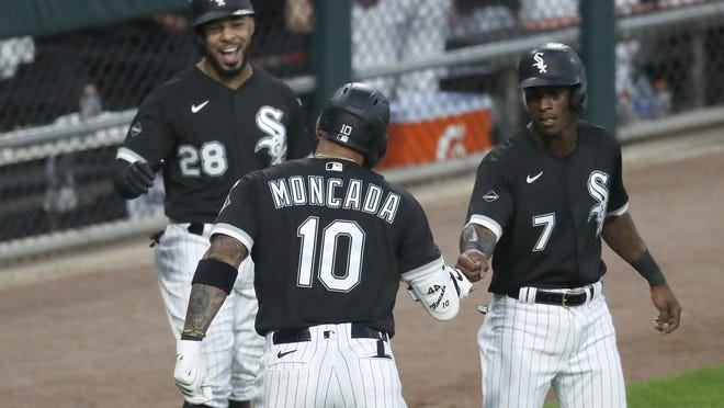Chicago White Sox's Yoan Moncada (10) is greeted outside the dugout by Leury Garcia (28) and Tim Anderson, after Moncada's three-run home run off Minnesota Twins starting pitcher Jose Berrios during the second inning Friday, July 24, 2020, in Chicago.