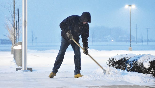 Light snow falls as maintenance employee Dennis McGowan shovels the main walkway at the entrance of Fort Loramie High School in Fort Loramie, Ohio, on Feb. 7, 2018. Another winter storm is forecast to hit the Midwest with heavy snow on Thursday and Friday.