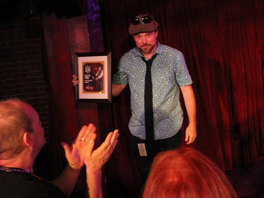 Paul Strickland, a Cincinnati-based playwright, storyteller and musician, accepts his Critic's Pick of the Fringe Award on Saturday night at the Know Theatre of Cincinnati. The award was voted on by critics covering the 2017 Cincinnati Fringe Festival.