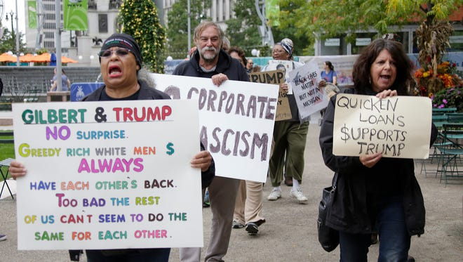 A group of protesters gather at Campus Martius and Compuware on Monday, Oct. 3, 2016, to protest a Donald Trump fund-raiser held last week in a downtown Detroit building owned by Dan Gilbert.