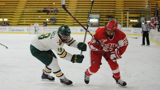 Catamount forward Val Caldwell (19) and Boston's Nina Rodgers (23) get tangled up battling for the puck during the women's hockey game between the Boston Terriers and the Vermont Catamounts at Gutterson Fieldhouse on Friday night November 17, 2017 in Burlington.