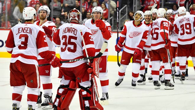 Red Wings players celebrate after the Wings' 5-4 overtime win on Sunday, Feb. 11, 2018, in Washington.