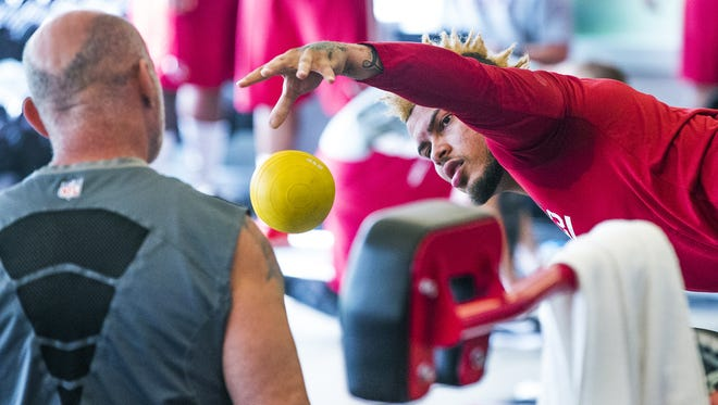 Strength and conditioning coach Buddy Morris, left,  observes Tyrann Mathieu at a Cardinals workout.
