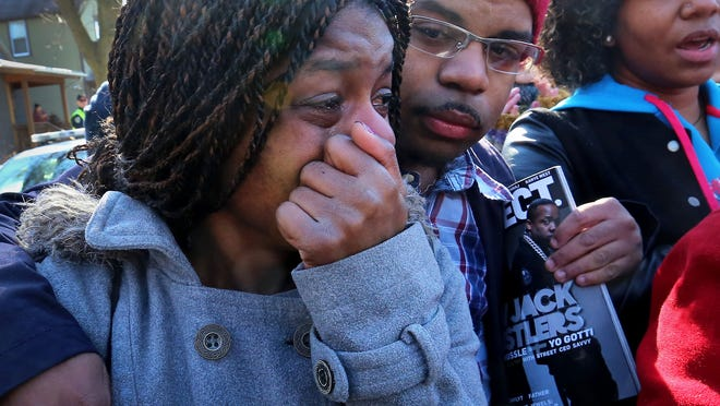 Kyrisha Isom, left, weeps with Derrick McCann during a rally protesting the shooting death of Tony Robinson, Saturday, March 7, 2015, in Madison, Wis. Robinson, an unarmed black 19-year-old, was fatally shot Friday by Matt Kenny, a white police officer, the Madison police chief said Saturday, March 7, 2015. Isom said she had been friends with Robinson for about 12 years.
