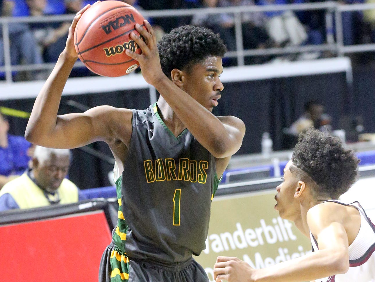 Hillsboro's Darius Ferguson (1) looks for an open player as he iis guarded by Memphis East's Nikcolauz Merriweather (0) during the State Tournament Quarterfinal game , on Wednesday at MTSU.