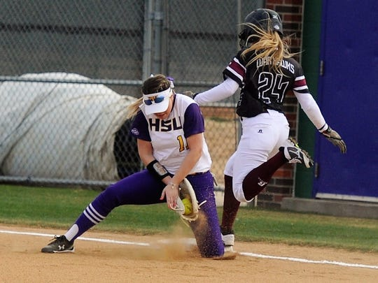 Hardin-Simmons first baseman Hillarie Carpenter (11) digs out a throw to get McMurry's Ashley McClellan (24) at first during the Wark Hawks' 7-6 win on Tuesday, Feb. 13, 2018.