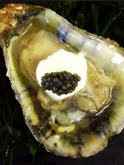 A cold Blue Point oyster served Russian style, with caviar and sour cream.
