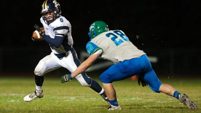 Essex's Cody Greene (6) tries to run past Colchester's Cody Turner (28) during the varsity football game between the Essex Hornets and the Colchester Lakers at Colchester High School on Friday night September 19, 2014 in Colchester.