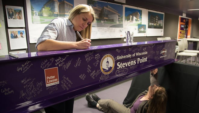 "Students, faculty and staff at the University of Wisconsin-Stevens Point were invited to sign the steel I-beam that will represent the tallest point of the new Chemistry Biology Building. Here, biology faculty members Jennifer Bray (standing) and Nancy Shefferly sign the beam. It will be placed during a ""topping out"" ceremony Monday, Feb. 27. Construction of the four-story academic building is on pace for completion in 2018."