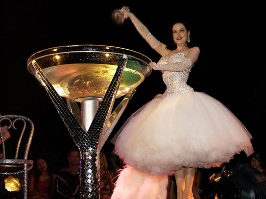 Dita Von Teese prepares a martini-glass striptease