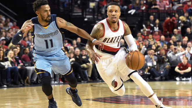 Portland Trail Blazers guard Damian Lillard, right, drives to the basket on Memphis Grizzlies guard Mike Conley, left, during the first half of an NBA basketball game in Portland, Ore., Monday, Jan. 4, 2016.