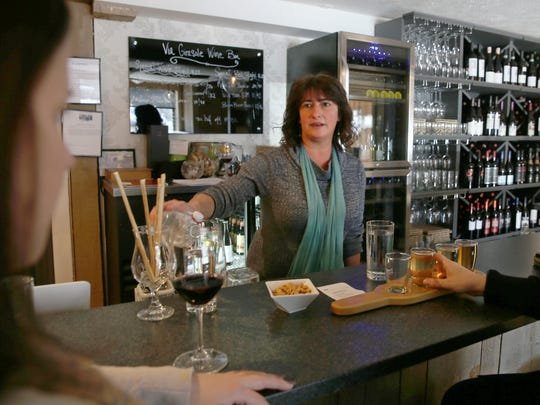 Susan Matack, manager of Via Girasole Wine Bar, waits on customers in the popular Schoen Place business in the village of Pittsford on Thursday.