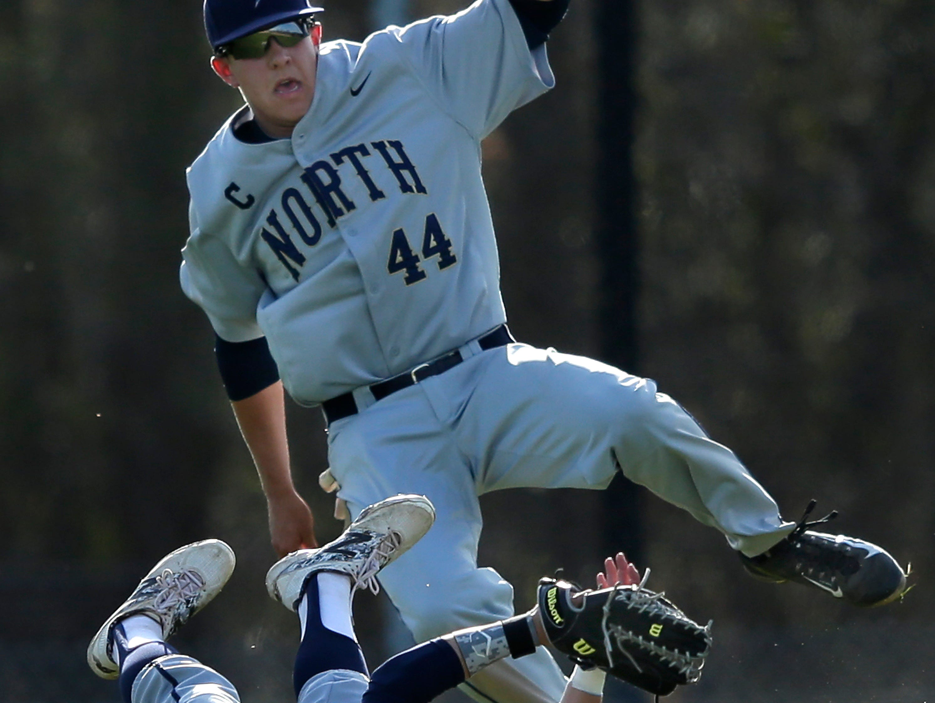 Appleton North High School center fielder Hunter Rolain (4) and second baseman Taylor Borchers (44) collide while chasing a fly ball during Tuesday's game against Kimberly High School in Kimberly.