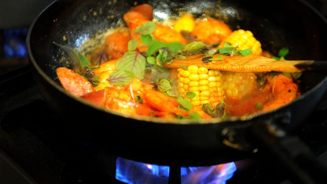 The signature dish at Prawn & Basil includes Cajun-style prawns, basil, corn, potatoes and sausages served on a sizzling plate.