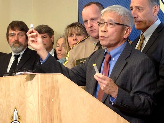 Dr. Harry Chen, state health commissioner, holds a