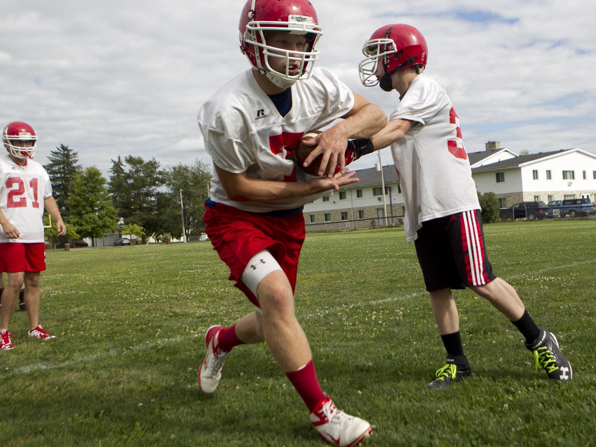 Pacelli football player Chris Shibilski, left, takes the hand off from Ben Lundgren, right, during the first day of football practice at Pacelli High School, Aug. 4.