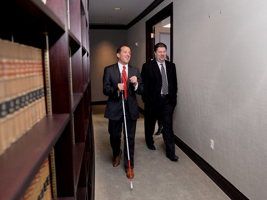 Bernstein uses a cane but not braille. Instead, he memorizes everything. He's outside his office with T.J. Bucholz of Vanguard Public Relations.